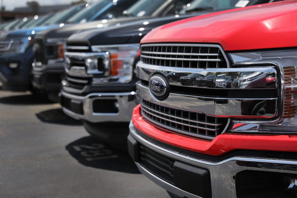 A row of Ford F-150 trucks sit on a dealership lot