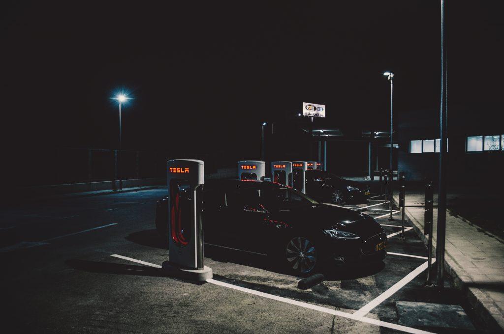 A black Tesla Model S sedan charging on a dark street in Barcelona