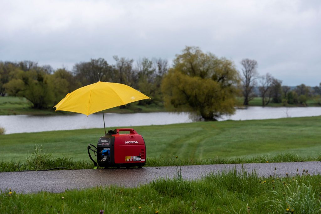 A Honda generator under a yellow umbrella on a trail next to a river