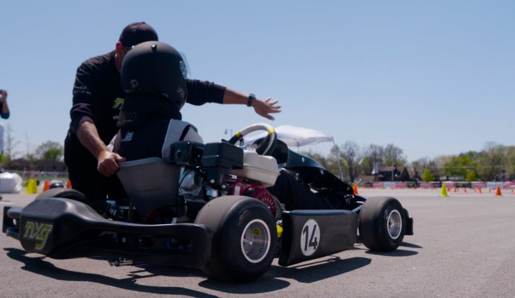 A man coaching a child on how to properly operate a go-kart