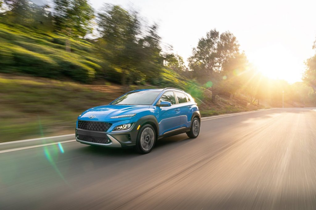 A blue Hyundai Kona driving, the Hyundai Kona is a cheap new car that offers an affordable base model