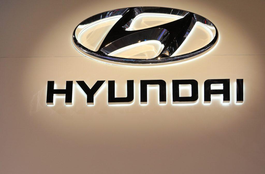 A black Hyundai logo against a beige background