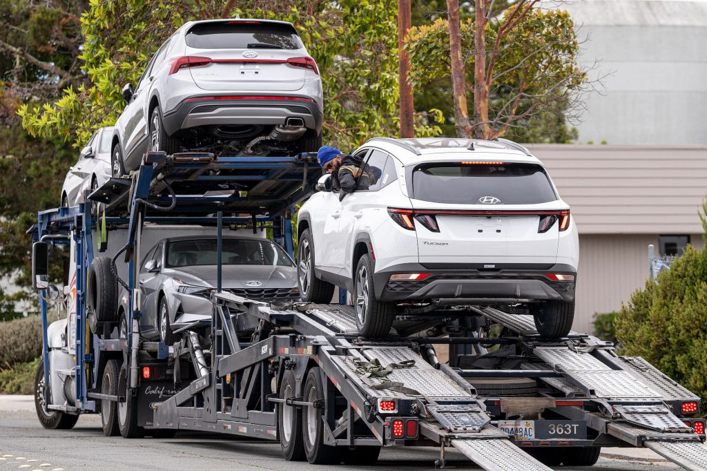 A worker unloads a Hyundai vehicle off of a transporter truck at a car dealership in Richmond, California, in July 2021