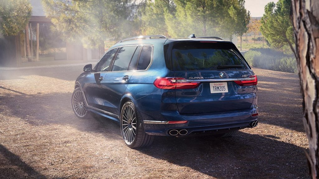 The back of a 2021 BMW X7 sits in a wooded clearing.