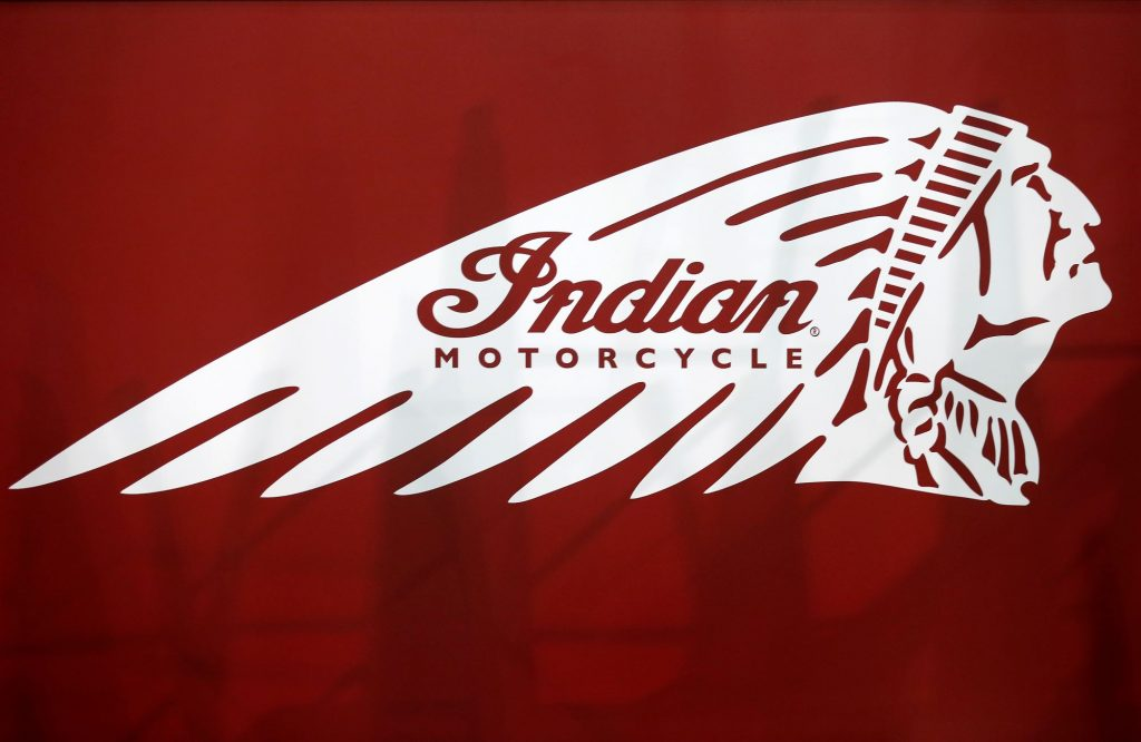 A white Indian Motorcycle logo on a red background with some vague shadows behind it.