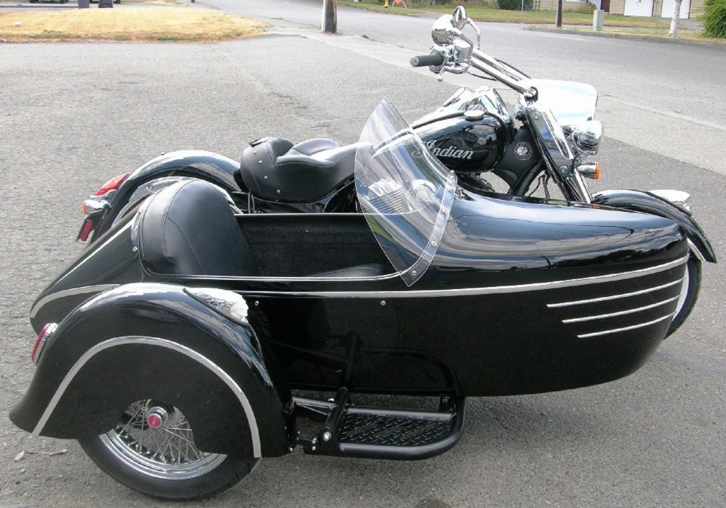 The side view of a black Indian Vintage with a black-and-chrome DMC Tomahawk sidecar