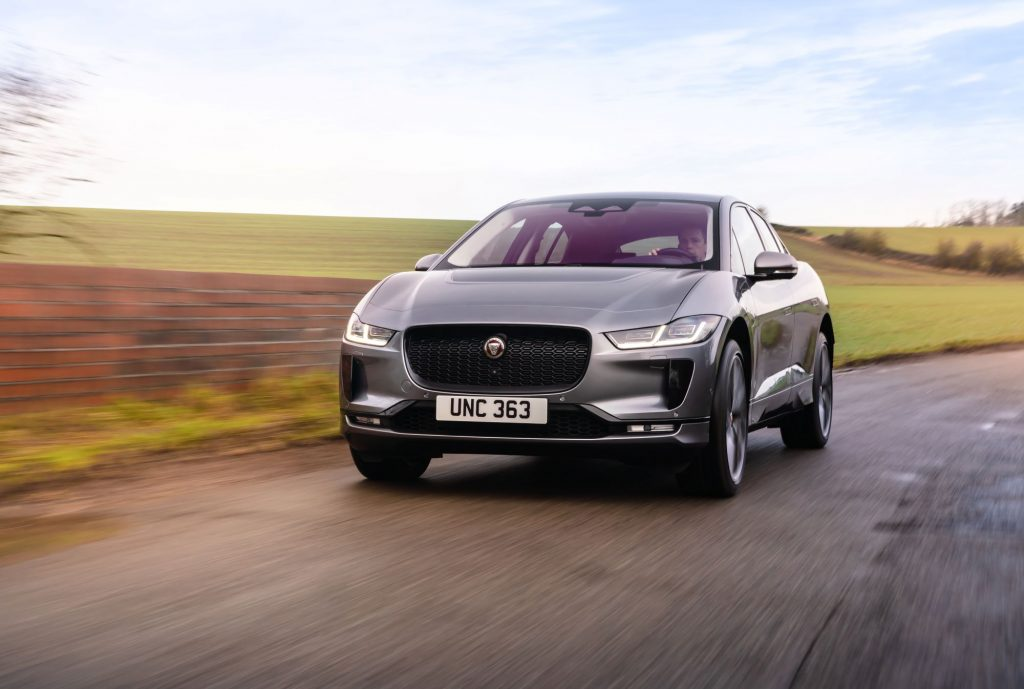 A silver Jaguar I-Pace driving on a highway with a background of green plains.