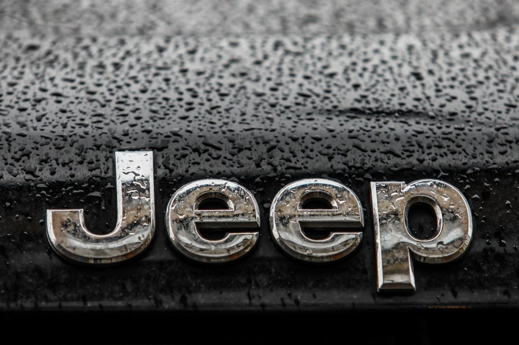 Jeep's logo in silver on a black car with raindrops.