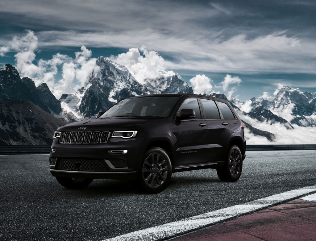 A black Jeep Grand Cherokee model parked on a racetrack near snowy and cloudy mountains