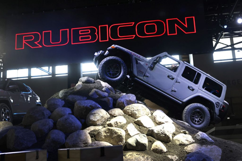 A grey Jeep Rubicon climbing a hill of large rocks with 'Rubicon' printed in red lettering filled in with black in the background.