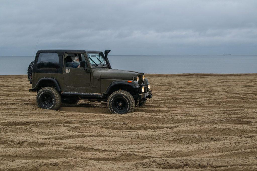 A Jeep Wrangler military model driving on a Baltic Sea coast beach