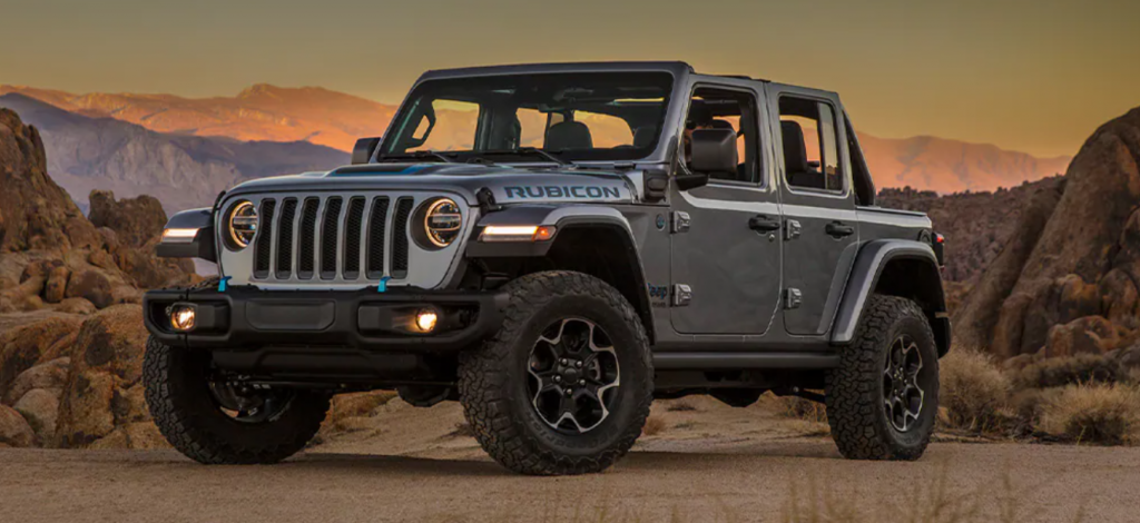 The Jeep Wrangler 4xe plug-in hybrid model parked in a desert and surrounded by rocks