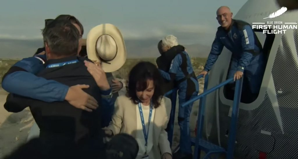 Jeff Bezos coming off the rocket New Shepherd with his crew dressed in space suits.