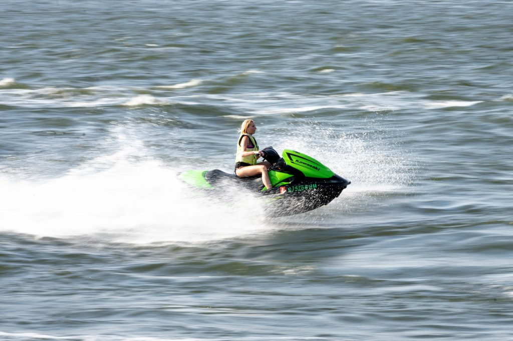 A woman rides a green Kawasaki Jet Ski on the East River in July 2020 in New York City