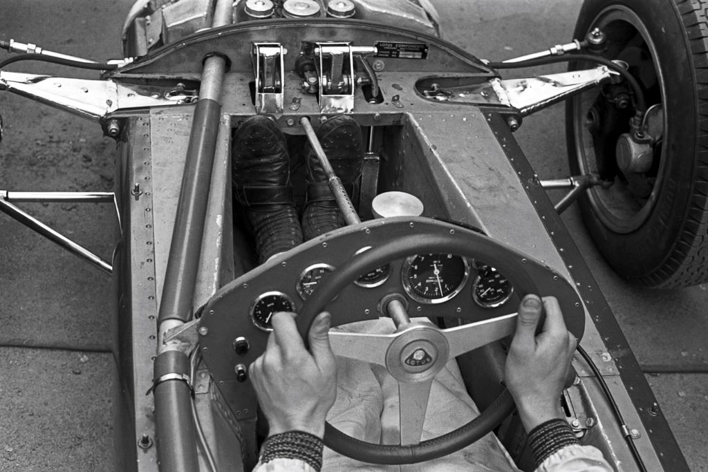 Jim Clark with his feet on two of the Lotus 25 F1 car's three pedals at the 1962 Grand Prix of Belgium