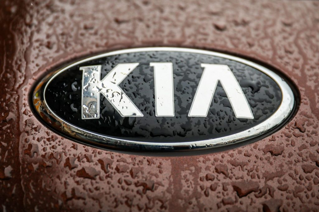 Close-up of the Kia logo on a burgundy color car with water raindrops.