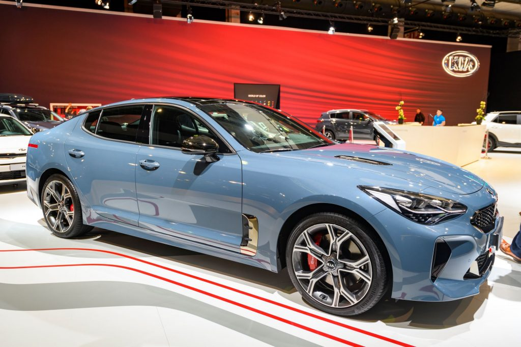 A light blue Kia Stinger at a 2020 reveal with a red background.