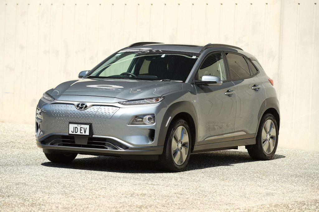 A silver Hyundai Kona Electric SUV parked in gravel outside a concrete building