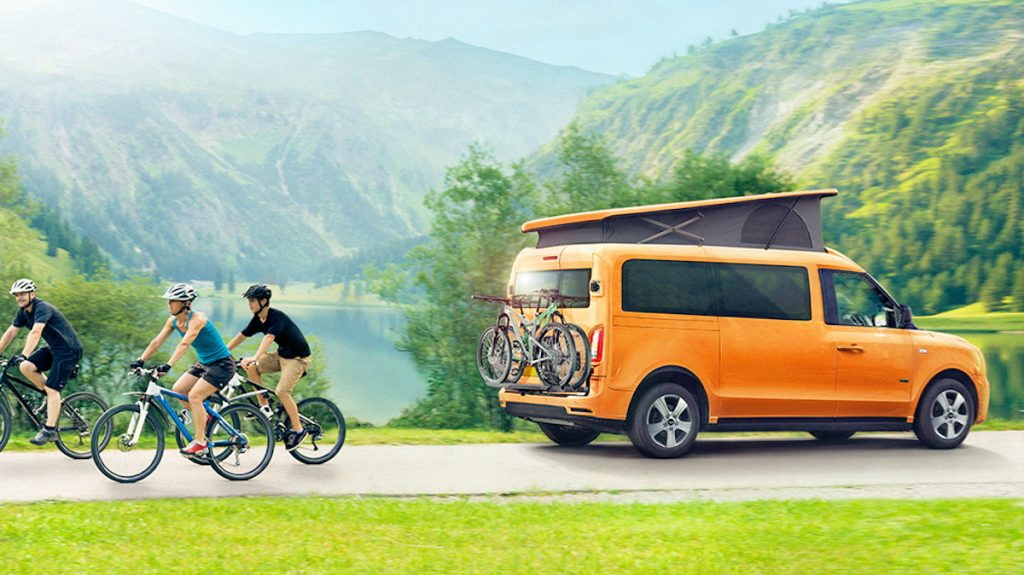 Tiny camper van with family cycling behind it
