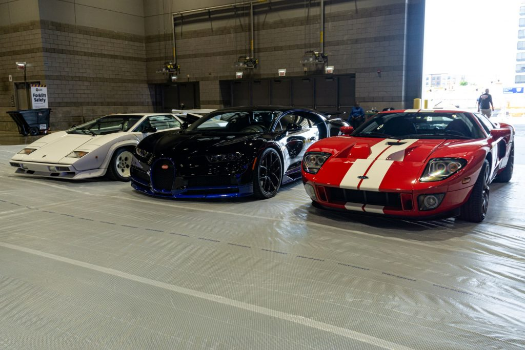 A white Lamborghini Countach 5000 S, black-and-blue Bugatti Chiron, and red-and-white Ford GT at the 2021 Chicago Auto Show