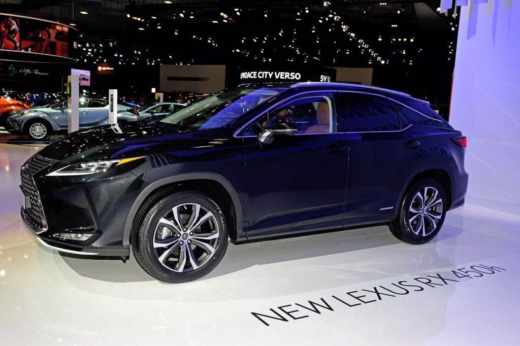"""A dark blue Lexus RX sitting in a showroom with other cars behind it on a white floor with black lettering stating """"New Lexus RX 450h"""" on the floor."""