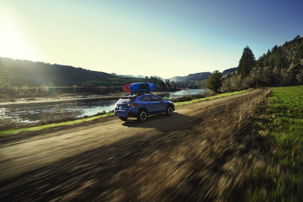 Blue Subaru Crosstrek driving down the road with two kayaks on the roof