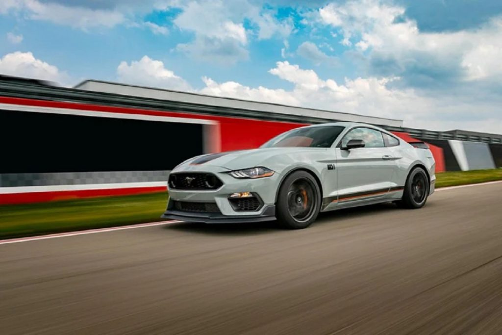 A light-colored 2021 Ford Mach-E races along a track. Ford's new gasoline perfume is inspired by the Mach-E.
