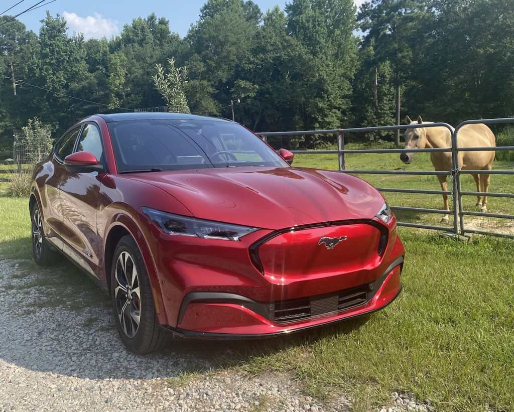 A red 2021 Ford Mustang Mach-E First Edition near a horse