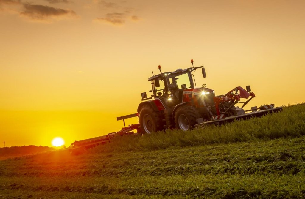 A Massey Ferguson 8S tractor working a hay field at sunrise