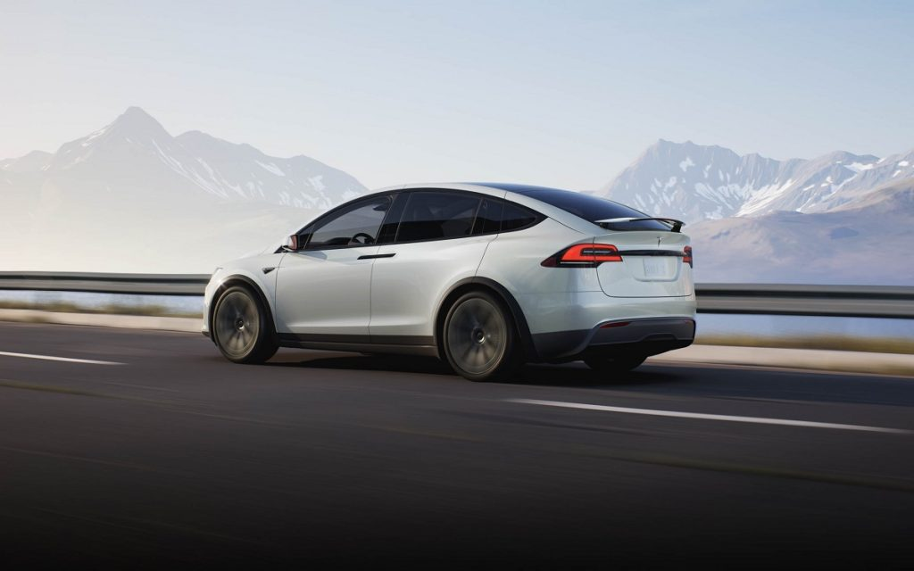 A white 2021 Tesla Model X drives down a highway.