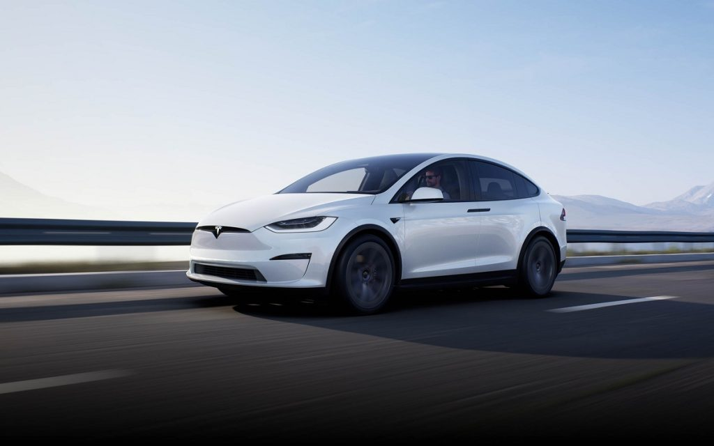 A white 2021 Tesla Model X driving down a highway.