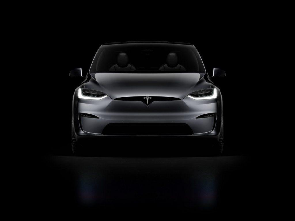 A dark gray 2021 Tesla Model X against a black background.