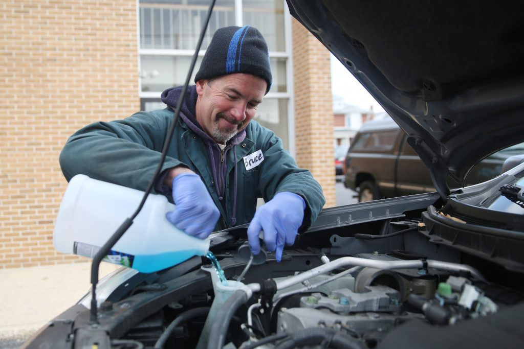 Man Maintaining Car By Filling it With Coolant