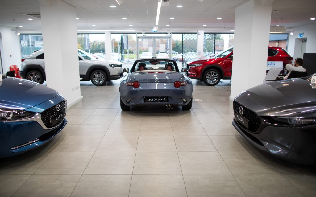 Various Mazda cars sit in a dealership style room with the back end of a grey Mazda MX-5 in the center, the front hood of a Mazda 2 on the right and a Mazda 3 on the left, with two crossover Mazda's in the back partially blocked by white pillars. All in front of a wall length window.