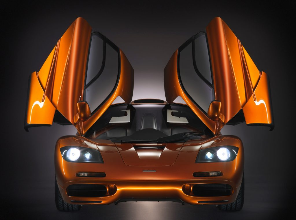A head-on view of an orange metallic McLaren F1 supercar with its gull-wing doors open