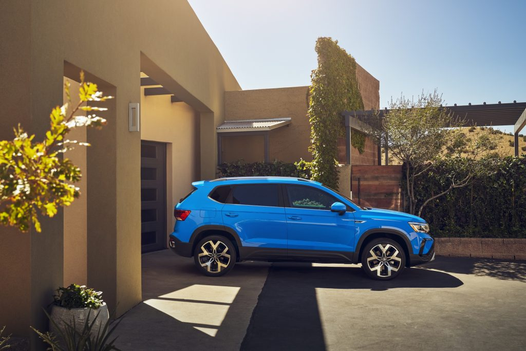 The new VW Taos in blue parked in front of a house
