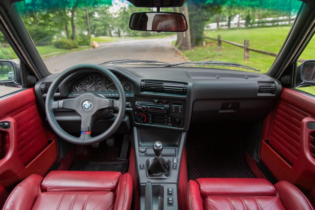 The modified red-leather front seats and black dashboard of a 1991 BMW 325iX