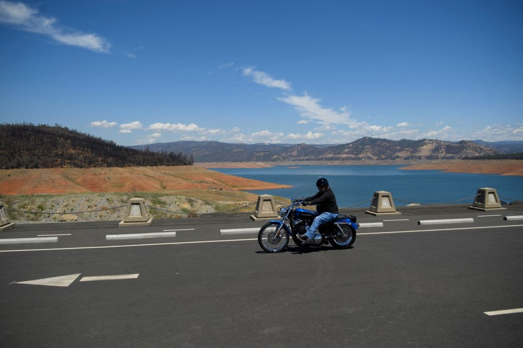 Motorcyclist riding on a black bike dressed in black over a bridge in California with a Mountainous landscape in the background and a brilliant blue body of water.