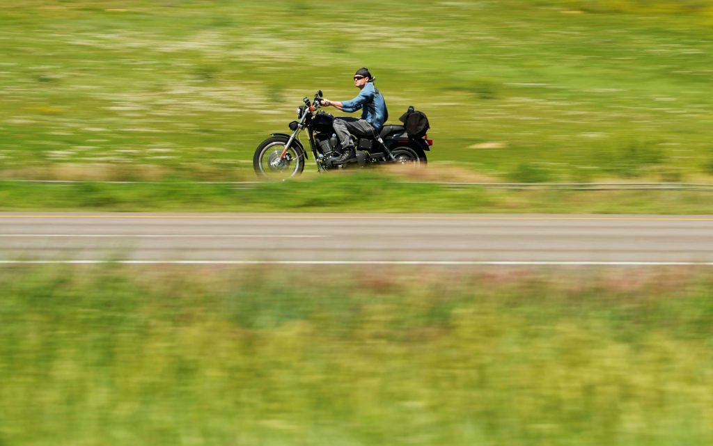 A man driving a motorcycle on the highway near grass fields and hills