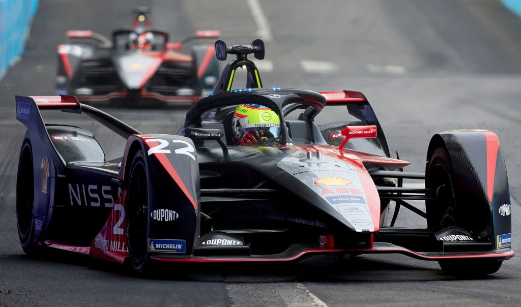 Nissan's black Formula E Racer coated in sponsor advertisements and logos driving around the track.