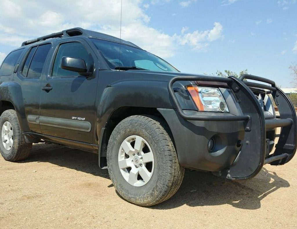 Nissan Xterra parked in the sand and happens to be one of the cheapest and best SUVs for someone looking for their first car.