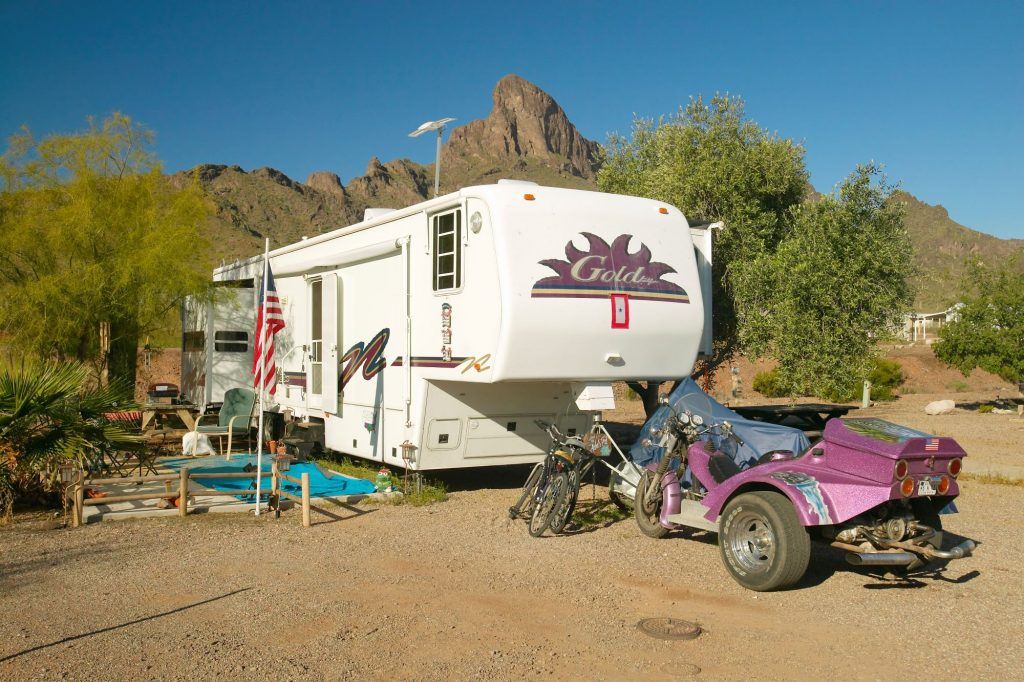 An off-road RV parked in a desert mountain area with an American flag, set of bikes, and an ATV