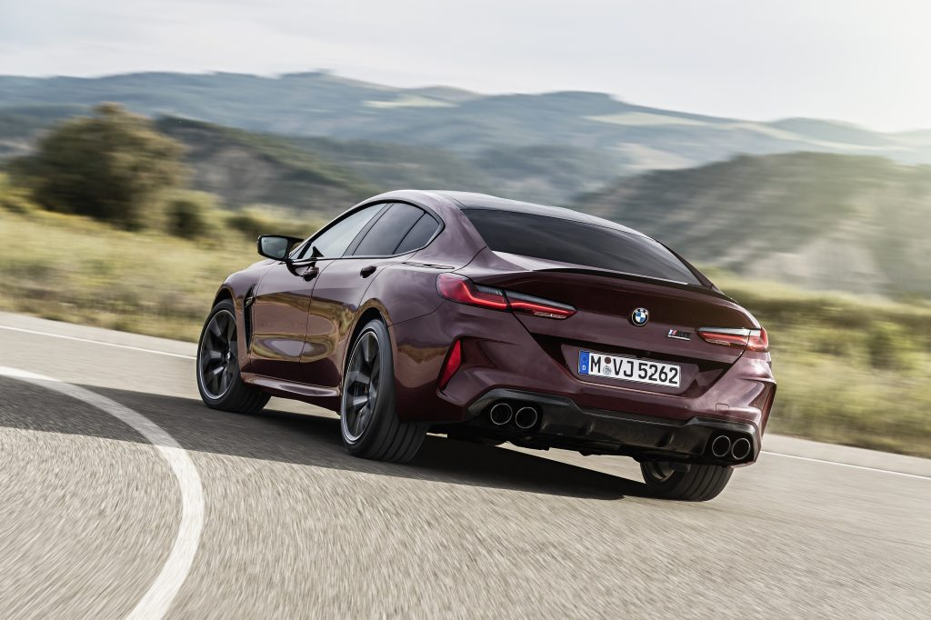 The rear of a maroon BMW M8 GC on a twisty section of road