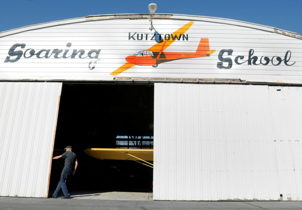 Thomas B. Edelstein of Fleetwood, the airport's licensed airplane mechanic, closes the main hangar doors, hiding a yellow 1940's Piper Cub. When you own a plane, you will need a place to store it