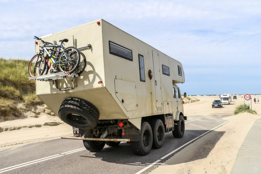 An RV Camper driving down a desert highway with bikes and a spare tire on its back