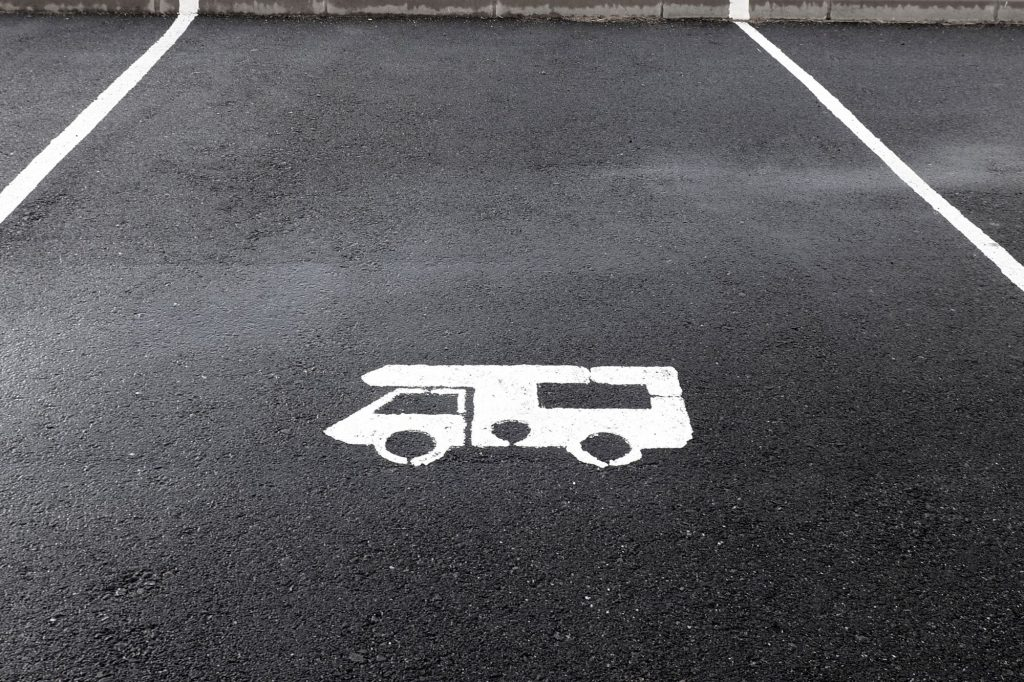 A blacktopped parking space with a white stencil sprayed representation of an RV.