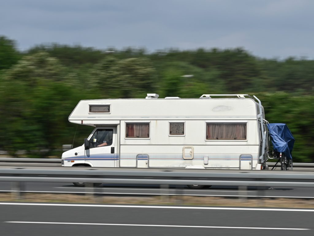 An RV travels on a road along a guardrail and trees