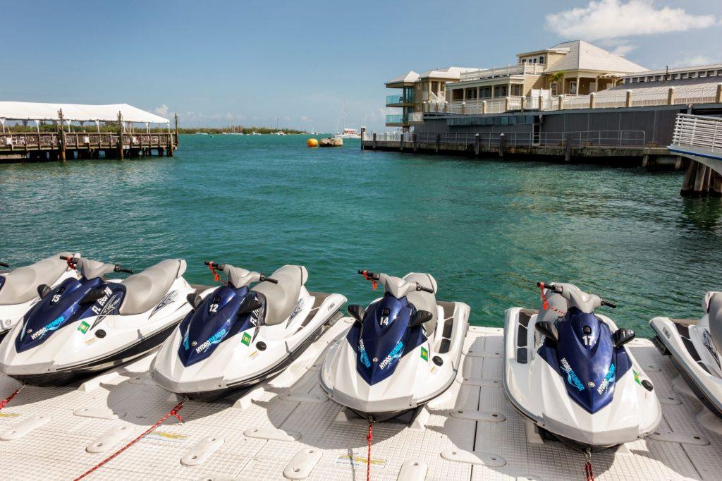 A row of rental jet skis on a marina