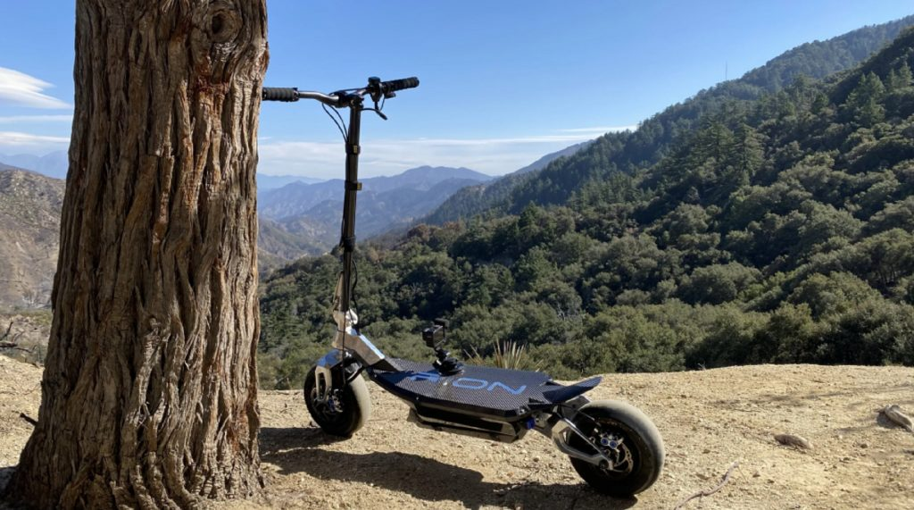 The rear 3/4 view of the carbon-fiber-and-aluminum Rion Thrust electric motorized scooter on a rocky hill