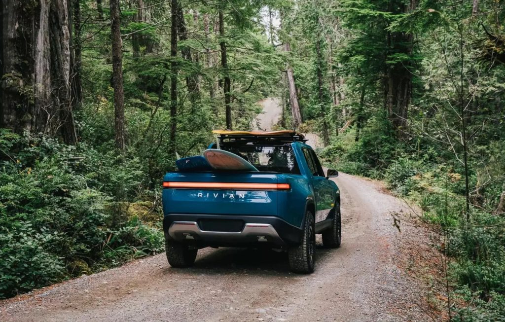 Rivian R1T driving through the woods with surfboards in the back